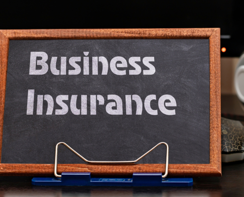 Business Insurance Services Concept. The text is written on a chalk board located at the workplace near the computer.